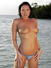 Cute brunette bikini babe posing on the beach