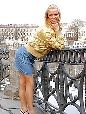 Sexy blonde hottie in blue jean miniskirt posing outside by river