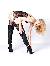 Kinky blonde wearing thigh high leather boots and a sexy fishnet suit showing her pussy