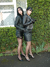 Two leather clad sluts pose outdoors