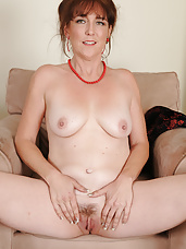 Elegant looking redhead Gypsy Lee pulling at her trimmed pussy hair