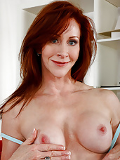 Horny mature redhead rides a young cock