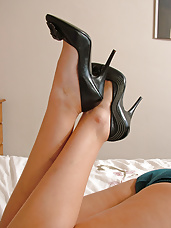 Cute Debbie on bed in silk sexy lingerie and shiny black stiletto heels