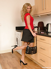 Hot babe Kathryn is teasing in the kitchen in shiny black heels and silky nylons